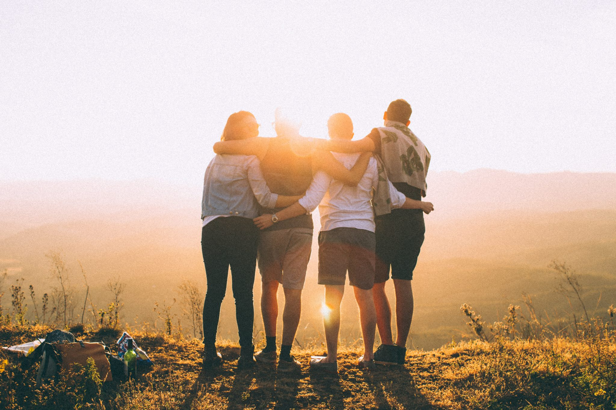 A group of young people with their arms around each other.