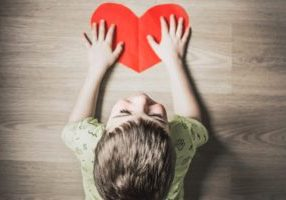 Child with special needs holds paper heart